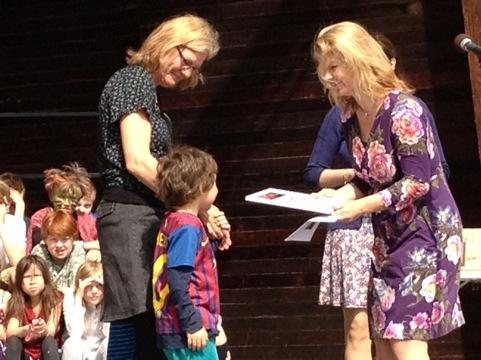 Två klasskompisar och läraren Lillemor tar emot priset av Lotta Edholm